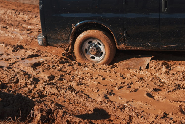 Tire of a black vehicle stuck in the mud